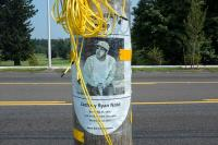memorial on light post with yellow rope and lines