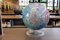 a globe of the moon inside a library