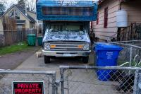 Blue RV with painting parked in driveway