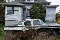 old car parked outside a house