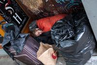 person with their possessions sleeping in a doorway