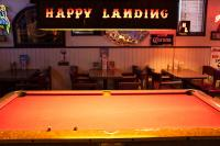 pool table and sign inside the Happy Landing Tavern